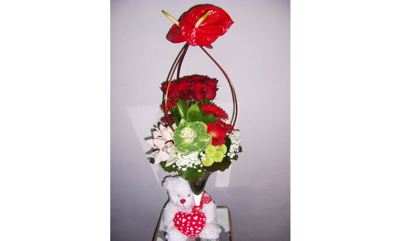 Valentine 14 - Impressive flower arrengement with a variety of flowers in a tall glass and in bright colors!